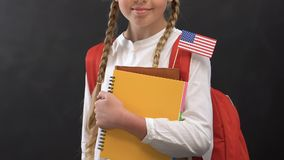 Nice girl with copy books and USA flag smiling at camera, language studying. Stock footage stock footage