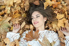 Nice girl covered with autumnal leaves. Young woman laying down on the ground covered by fall foliage in park. Beautiful sexy girl Royalty Free Stock Photos