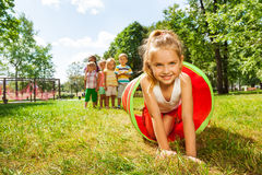 Nice girl crawling thought the tube in park Royalty Free Stock Photos