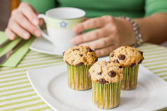Nice girl with a cup and chocolate chip muffin at breakfast. Nice girl with a cup and delicious chocolate chip muffin at breakfast in green striped tablecloth Royalty Free Stock Images
