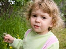 Nice girl with a dandelion. In the garden Stock Photos