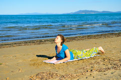 Nice girl doing yoga excercise on the beach Royalty Free Stock Image