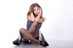 Nice girl in dress sits Royalty Free Stock Image