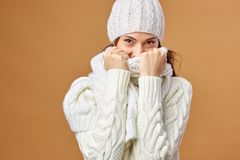 Nice girl dressed in white knitted sweater and hat closes her face with white scarf on a beige background in the studio.  stock images