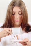 The nice girl with a drink mug. The nice girl in white with a mug of a drink and a saucer Stock Photos