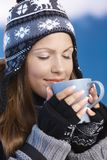 Nice girl drinking hot tea in winter eyes closed. Pretty young girl dressed up warm for skiing wearing cap and gloves drinking hot drink eyes closed front of Stock Image