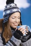 Nice girl drinking hot tea in winter eyes closed. Pretty young girl dressed up warm for skiing wearing cap and gloves drinking hot drink eyes closed front of Royalty Free Stock Photography