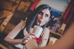 Nice girl drinking smoothie with her friend royalty free stock photo