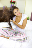 Nice girl drying hair at home in her room Stock Images
