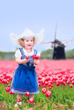 Nice girl in Dutch costume in tulips field with windmill. Adorable curly toddler girl wearing Dutch traditional national costume dress and hat playing in a field Stock Image