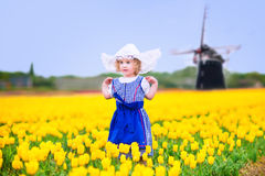 Nice girl in Dutch costume in tulips field with windmill. Adorable curly toddler girl wearing Dutch traditional national costume dress and hat playing in a field Stock Photos