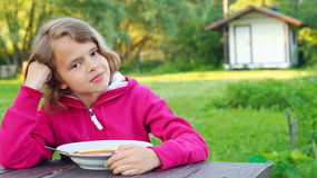 Nice girl eating a soup outdoors Royalty Free Stock Images