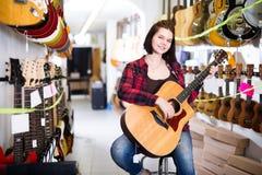 Nice girl examining various acoustic guitars. In guitar shop Stock Photo
