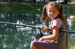 Nice girl with the fishing rod on the shores of lake fishing 3 Royalty Free Stock Photography