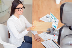 Nice girl getting package from the robot Royalty Free Stock Image