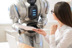 Nice girl getting papers from robot Stock Image