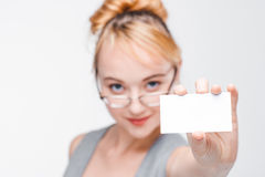 Nice girl in glasses shows empty card closeup. Nice young girl in glasses and vest showing white empty card with copy space. Blurred portrait on grey background Stock Photo