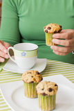Nice girl hand taking chocolate chip muffin at breakfast. Nice girl hand taking delicious chocolate chip muffin at breakfast in green striped tablecloth Stock Photos