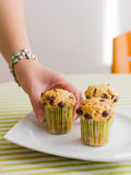Nice girl hand taking chocolate chip muffin at breakfast. Nice girl hand taking delicious chocolate chip muffin at breakfast in green striped tablecloth Royalty Free Stock Images