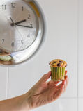 Nice girl hand taking chocolate chip muffin at lunch with clock. Nice girl hand taking delicious chocolate chip muffin at lunch with metalic clock in background Stock Photo