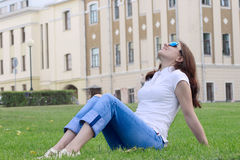 The nice girl having a rest on a grass. The nice girl in sun glasses having a rest on a green grass Stock Images