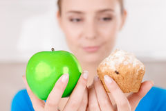 Nice girl holding apple and muffin. What to eat. Selective focus of muffin and apple in hands of charming pretty young girl holding it and going to eat while Royalty Free Stock Photo