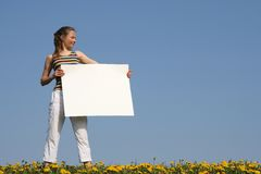 Nice girl holding blank banner. Nice girl in a flowering field, holding blank white cardboard with copy space Royalty Free Stock Photo