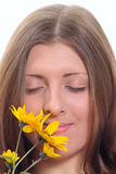 The nice girl inhaling aroma of a flower. Portrait of the nice girl inhaling aroma of a yellow flower removed close up Stock Photos