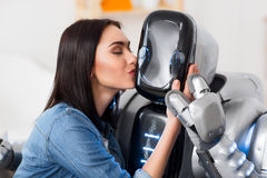 Nice girl kissing robot. Edge between fiction and reality. Cheerful delighted beautiful girl kissing robot and closing her eyes while resting together stock photo