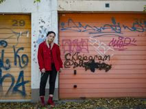 Nice girl in a knitted hat, a red jacket and red boots stands near the gate of the garage with graffiti stock photography