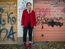 Nice girl in a knitted hat, a red jacket and red boots stands near the gate of the garage with graffiti stock photo