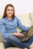 Nice girl at laptop home. Pretty one. Girl with nice smile sitting at laptop on sofa home Stock Photo