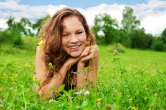 Nice girl laying on green grass Stock Photos