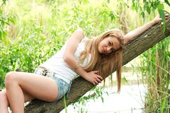 Nice girl lays on the tree Stock Images
