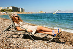 Nice girl lying on chaise on the beach. At the sea resort royalty free stock photos