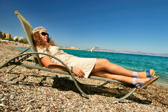 Nice girl lying on chaise on the beach. At the sea resort stock photography