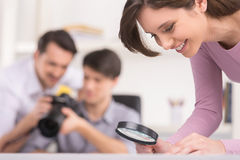 Nice girl with magnifier on the foreground. Stock Images