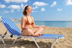 Nice girl meditating on the beach. On the chair stock photos