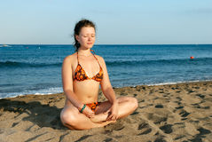 Nice girl meditating on the beach. At evening royalty free stock photo