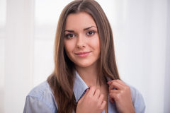 Nice girl in the morning. Half-length portrait of dark-haired beautiful smiling girl wearing blue shirt touching it looking at us waking up in the morning Stock Photos