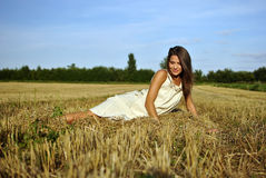 Nice girl in national dress sitting on a field Stock Image