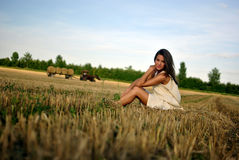 Nice girl in national dress sitting on a field Stock Images