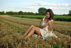 Nice girl in national dress sitting on a field Stock Photography