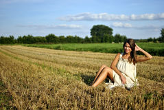 Nice girl in national dress sitting on a field Royalty Free Stock Photos