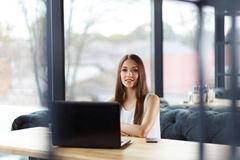 A nice girl in the office. A nice girl works hard, siiting in front of her laptop screen with the huge window on the backfground stock images