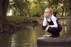 Nice girl outdoor at autumn. Little preteen girl sitting near the lake with ducks in park at autumn Stock Image