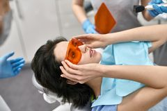 Pretty woman`s teeth treatment in dental clinic stock images