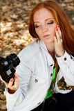 Nice girl photographer taking selfe in autumn park. Nice pretty girl taking selfe in autumn park with foliage Stock Photo