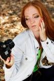 Nice girl photographer taking selfe in autumn park Stock Photo