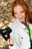 Nice girl photographer taking selfe in autumn park Stock Image